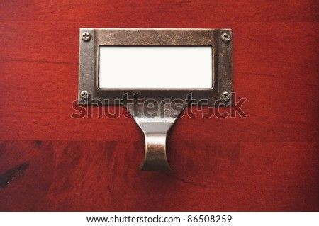Lustrous Wooden Cabinet with Blank File Label in Dramatic LIght. - stock photo