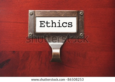 Lustrous Wooden Cabinet with Ethics File Label in Dramatic LIght. - stock photo