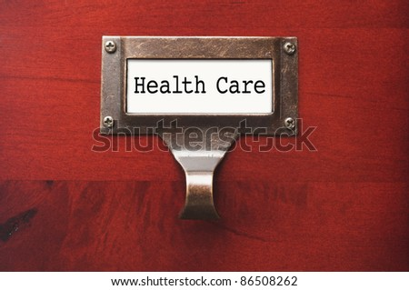 Lustrous Wooden Cabinet with Health Care File Label in Dramatic LIght. - stock photo