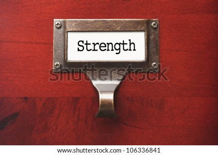 Lustrous Wooden Cabinet with Strength File Label in Dramatic Light. - stock photo