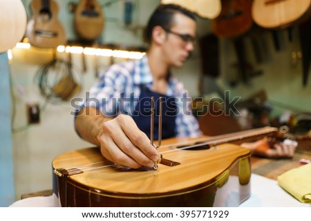 Lute maker shop and classic music instruments: young adult artisan fixing old classic guitar, tuning the instrument with a metallic diapason. Closeup of hand on guitar body - stock photo