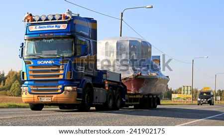 LUVIA, FINLAND - SEPTEMBER 19, 2014: Scania R500 hauls a wide load. If the width of the transport exceeds 3.5 metres, the maximum permissible speed on Finnish roads is 60 km/h. - stock photo