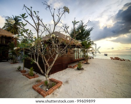 Luxiry villa on a tropical beach at sunrise - stock photo