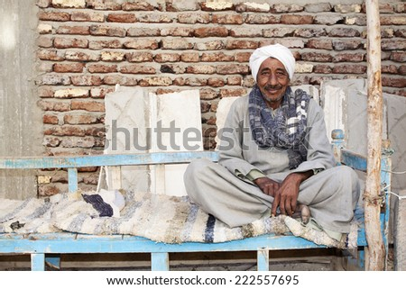 LUXOR, EGYPT - December 19: Elderly unidentified man siting on bench in Luxor.  He is happy to be there for tourist photographers. Photo taken on December 19, 2011 - stock photo
