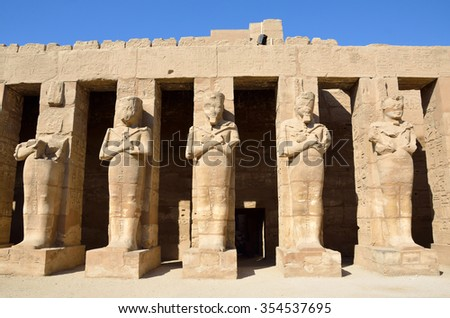 LUXOR, EGYPT - DECEMBER 4 2015:  Ramesses III Temple is in the Karnak Temple complex and the court of it is surrounded by statues of him.