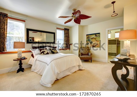 Luxuriant bright bedroom with contrast dark brown wooden furniture - stock photo
