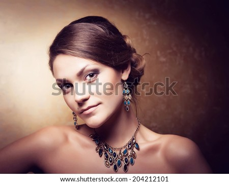 Luxurious accessories concept. Glamour portrait of beautiful woman with earrings and necklace on the bared shoulders. Close up. Studio shot - stock photo