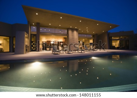 Luxurious and modern house with swimming pool at night - stock photo
