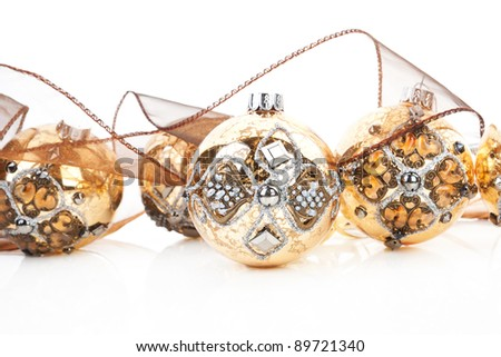 Luxurious antique golden christmas balls decorated with brown ribbon. Traditional festive xmas background.