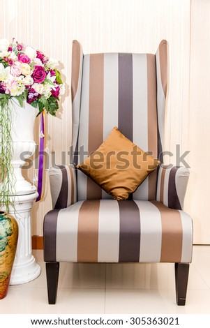 Luxurious armchair with artificial flower - stock photo