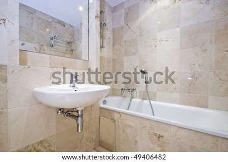 Luxurious bathroom detail with a classy bath tub, wash basin and stone tiled walls - stock photo