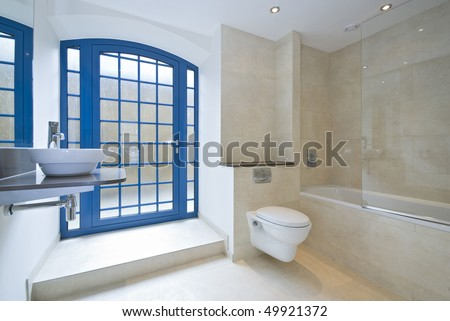Luxurious bathroom detail with a designer ceramic wash basin, large bath tub and stone tiled walls - stock photo