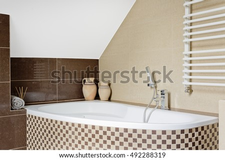 Luxurious bathroom interior in brown with mosaic tile bathtub
