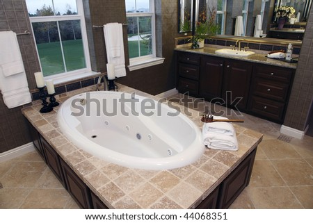 Luxurious bathroom with a modern tub and golf course view. - stock photo