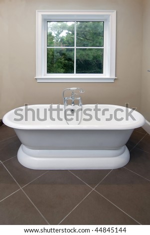 luxurious bathtub in white and chrome with window - stock photo