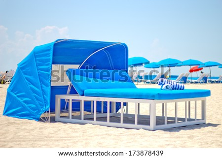 Luxurious beach bed with canopy on a sandy beach - stock photo
