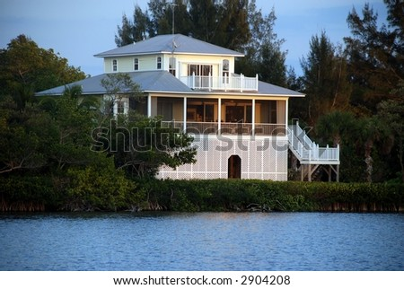luxurious beach vacation house at sunset - stock photo
