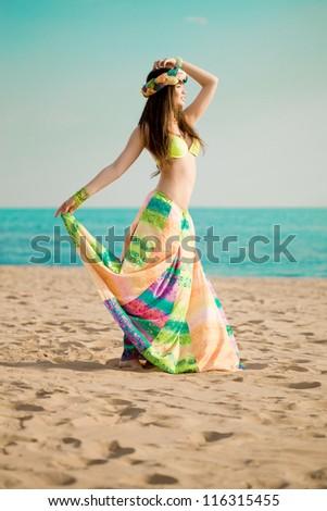 Luxurious beautiful fashionable woman on the beach at sun - stock photo
