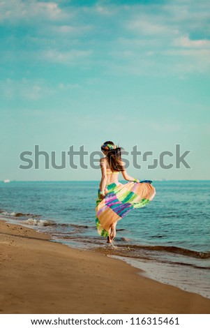 Luxurious beautiful fashionable woman runs along the beach - stock photo