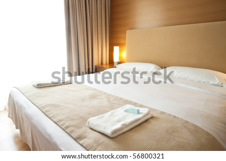 Luxurious bedroom with two towels on the bed - stock photo