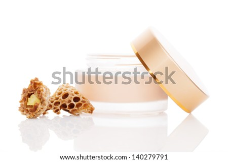 Luxurious beeswax cosmetic background. Cream in jar and natural royal jelly isolated on white background. Feminine skin care concept. - stock photo
