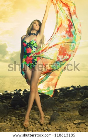 Luxurious blonde in color dress on the beach - stock photo