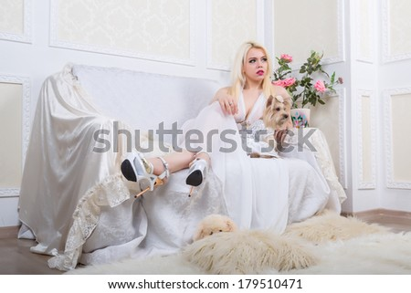Luxurious blonde woman in a white dress with a dog  pekingese in front of modern classical room