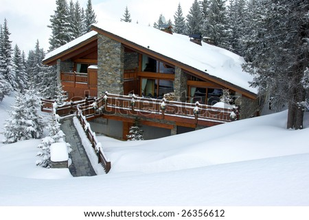 Luxurious chalet covered with snow in a skiing resort. - stock photo