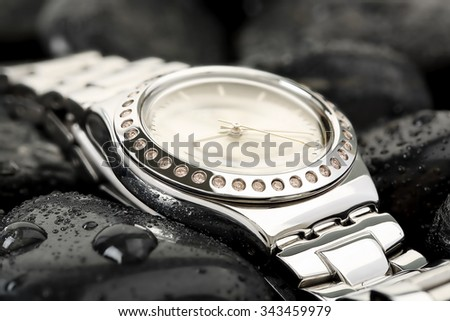 luxurious chrome watch on black stones with water drops - stock photo