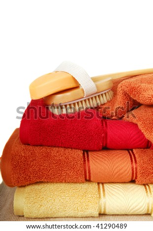 Luxurious cotton towels with a scrubbing brush and scented soap - stock photo