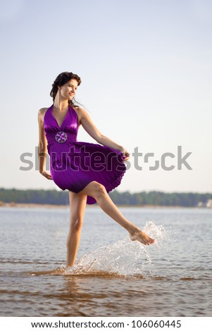 Luxurious dancing woman on the background of the sea, outdoors - stock photo