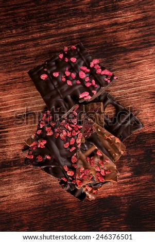 Luxurious dark and milk chocolate pieces in dark brown textured wooden background. Sweet chocolate dessert eating.  - stock photo