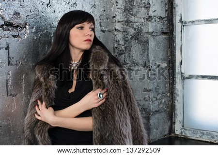 Luxurious dark-haired young female in fur coat standing by the window and looking away, horizontal shot - stock photo