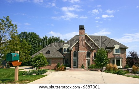 Luxurious executive home with blue sky and mailbox - stock photo