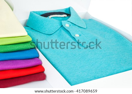 Luxurious fine material 100% cotton polo shirt displayed in gift box with a pile of another polo shirts in many different colors
