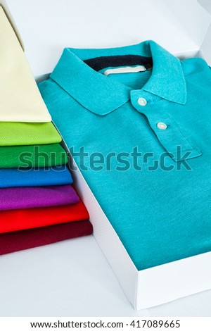 Luxurious fine material 100% cotton polo shirt displayed in gift box with a pile of another polo shirts in many different colors  - stock photo