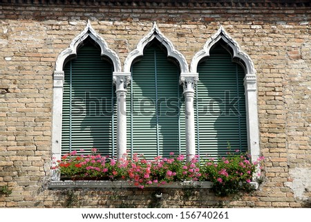 luxurious flowery balcony in Venetian style with arched windows of a historic residence in Venice - stock photo