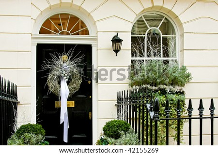 Luxurious front door with conifer Christmas wreath - stock photo