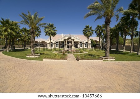Luxurious Home with large front yard and  driveway with tropical trees and foliage. - stock photo