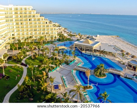 Luxurious hotel with a swimming pool at Cancun, Mexico. Perfect  tropical vacation. Caribbean Sea. Sunrise. - stock photo