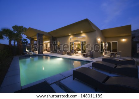 Luxurious house with swimming pool at night - stock photo