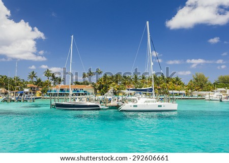 Luxurious image of two sailboats on the dock near the beach - stock photo