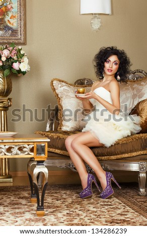 Luxurious Lady sitting on Retro Couch with Cap of Coffee. Classic Interior - stock photo