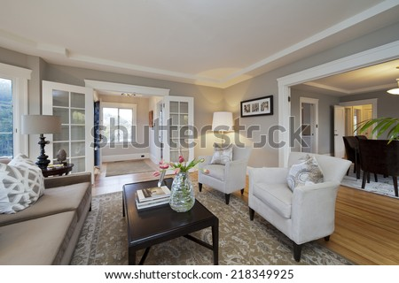 Luxurious living room with white wooden trimming, couch, rug, wooden floor and open glass doors leading into dining area in sumptuous style home. - stock photo