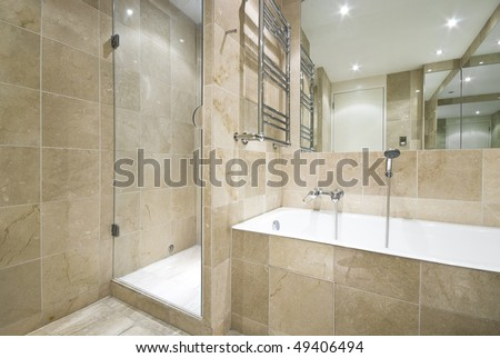 Luxurious marble bathroom with a large classy bath and shower - stock photo