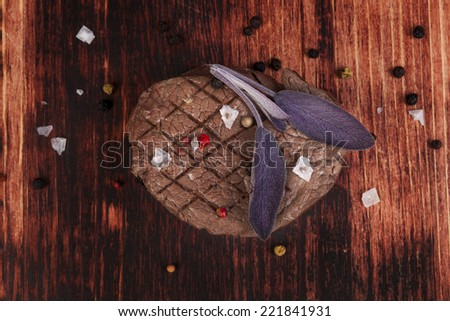 Luxurious mignon steak with colorful peppercorns and salt flakes on dark wooden background, top view. Barbeque red meat eating. Culinary steak, fine dining. - stock photo
