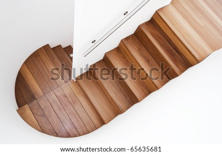 luxurious modern wooden staircase with curved landing wall - stock photo