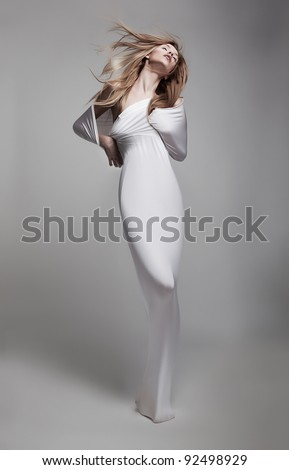 Luxurious mystical young Woman in White clothes with Waving Long Hair gracefully posing in studio. Advertisement Sales concept. Poster Art Design - stock photo