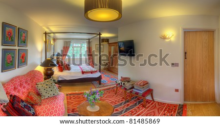 Luxurious red bedroom with four poster bed (Sussex Prairies B&B) - stock photo