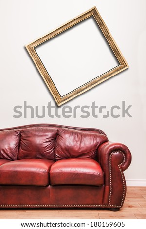 Luxurious Red Leather Couch in front of a blank crooked frame to ad your text, logo, images, etc. - stock photo